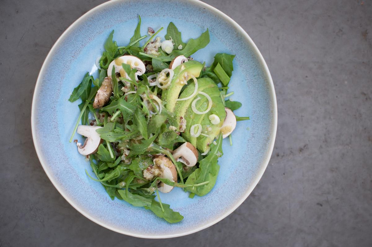 blauer Teller mit Salat aus Ruccola, Avocado, Quinoa und Pilzen von oben