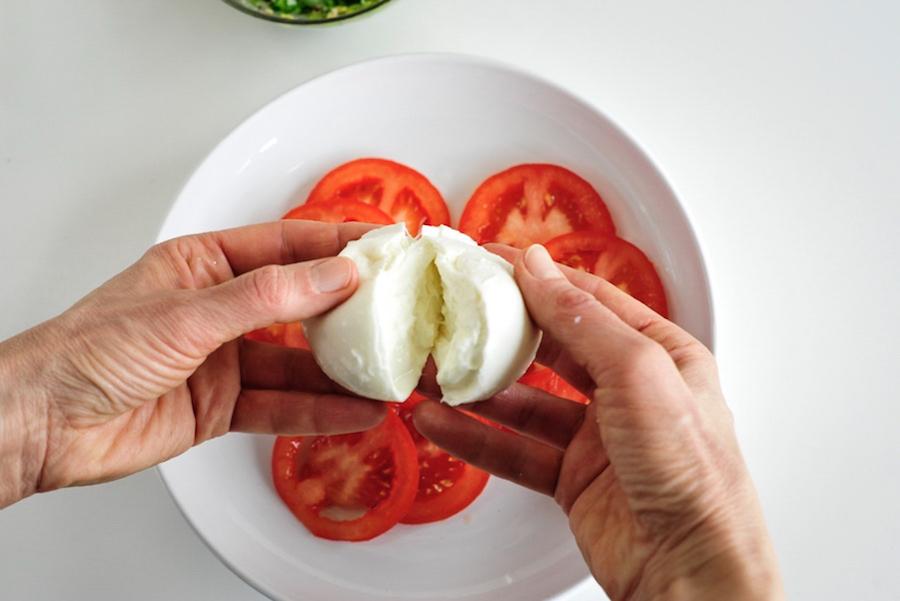 Tomaten auf weißem Teller und Büffelmozzarella in Händen