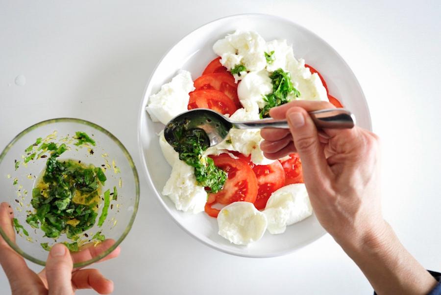 Tomaten und Büffelmozzarella auf weißem Teller mit Dressing auf Basilikum