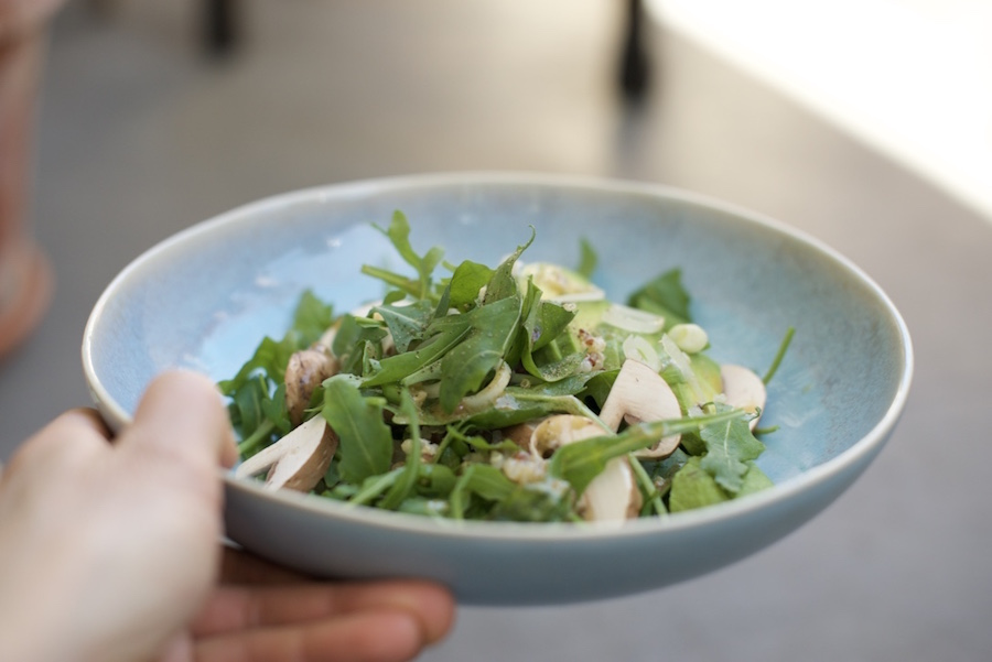 blaue Salatschale mit Salat aus Ruccola, Champignons, Avocados und Quinao