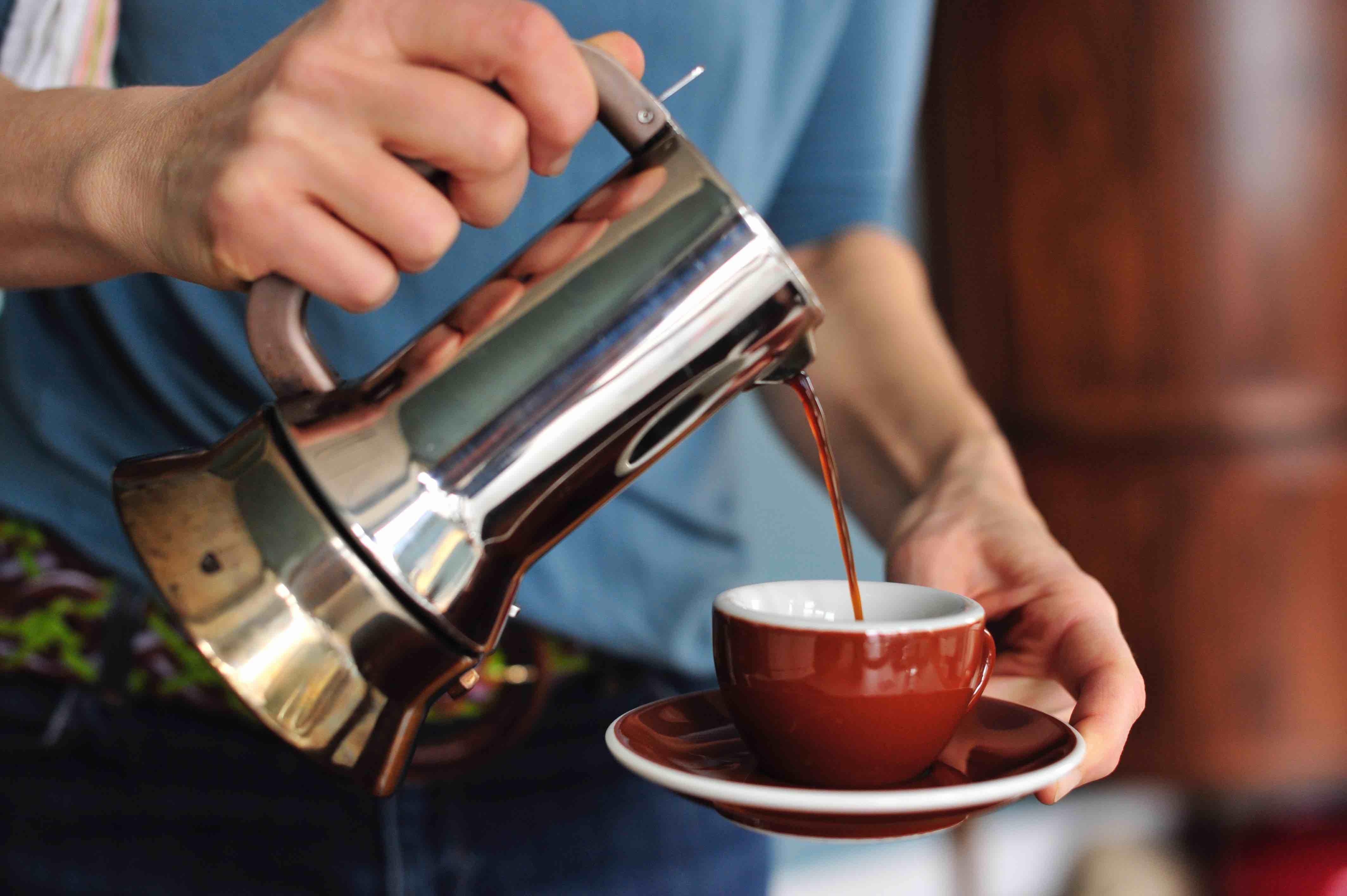 Espresso einschenken mit Espressokanne und Espressotasse