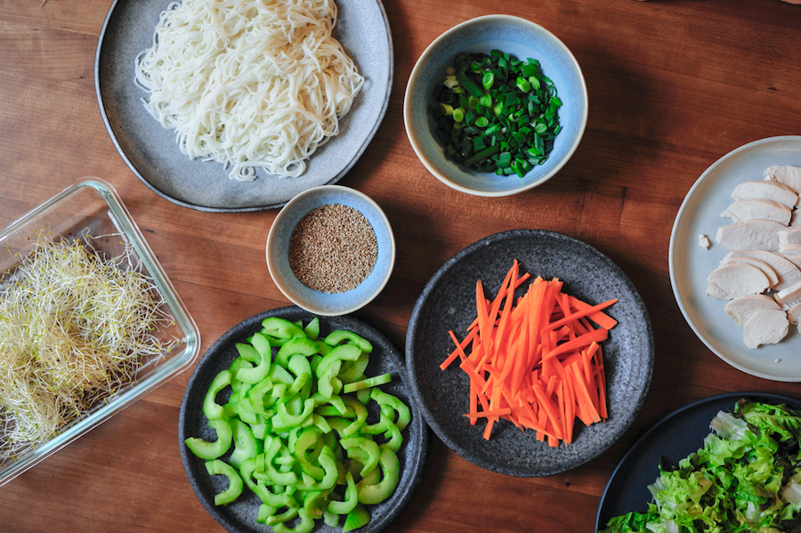 Teller mit Salat, Möhren, Reisnudeln, Frühlingszwiebeln, Hühnchen, Tofu für glutenfreie Frühlingszwiebeln