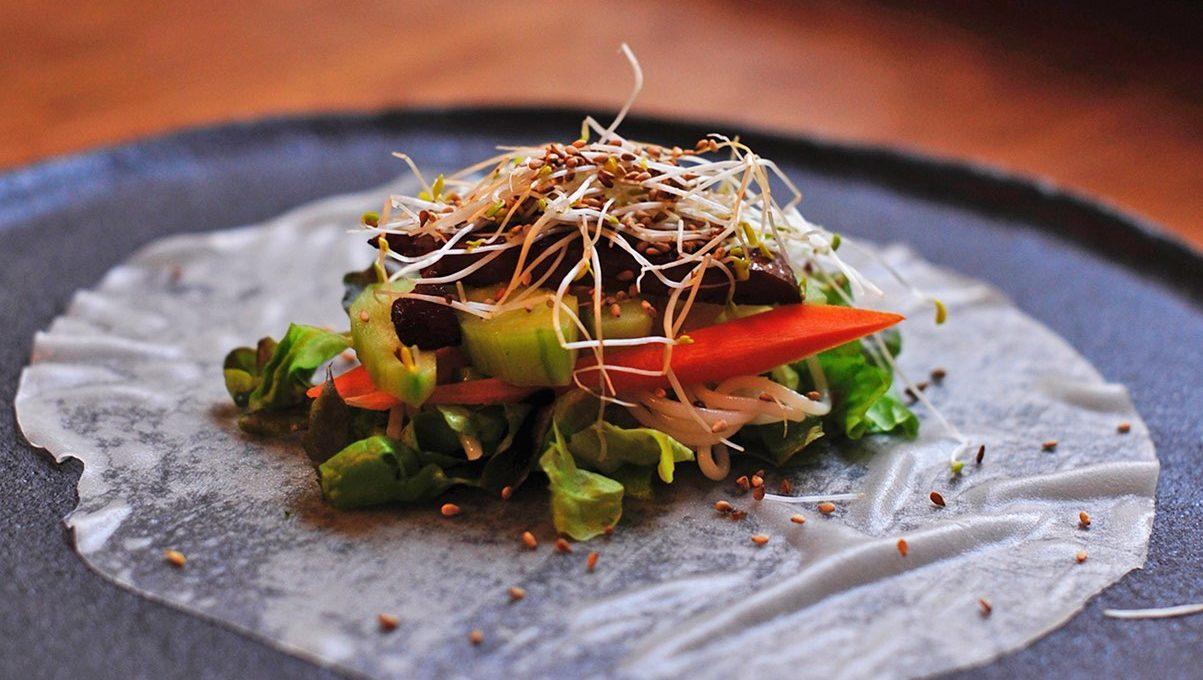Teller mit Reispapier und Füllung aus Salat, Möhren, Reisnudeln, Frühlingszwiebeln, Tofu