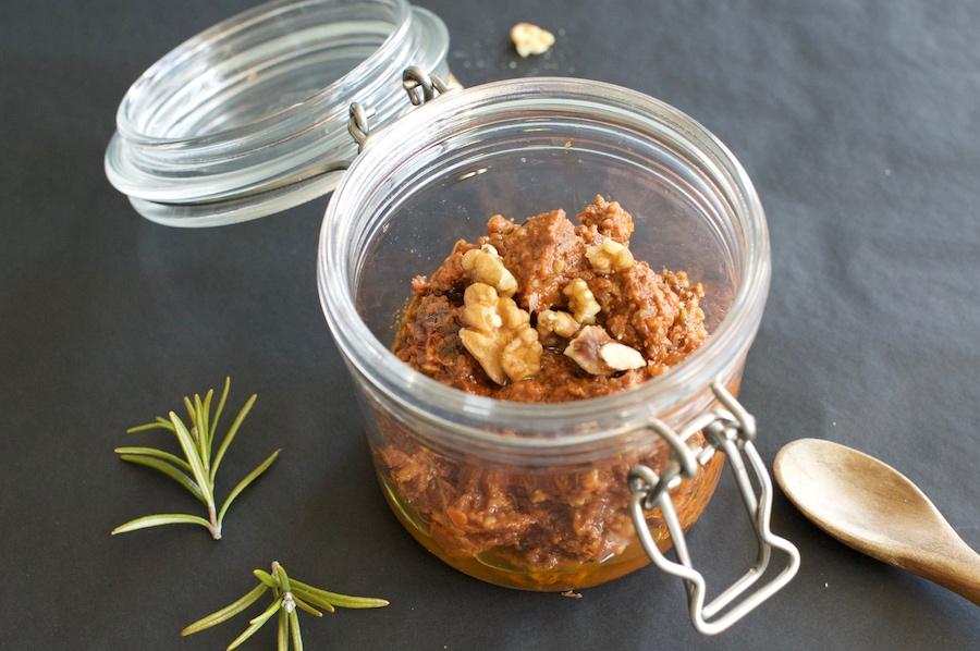 Offenes Glas mit rotem Pesto aus Walnüssen, Knoblauch, Tomatenmark und Rosmarin