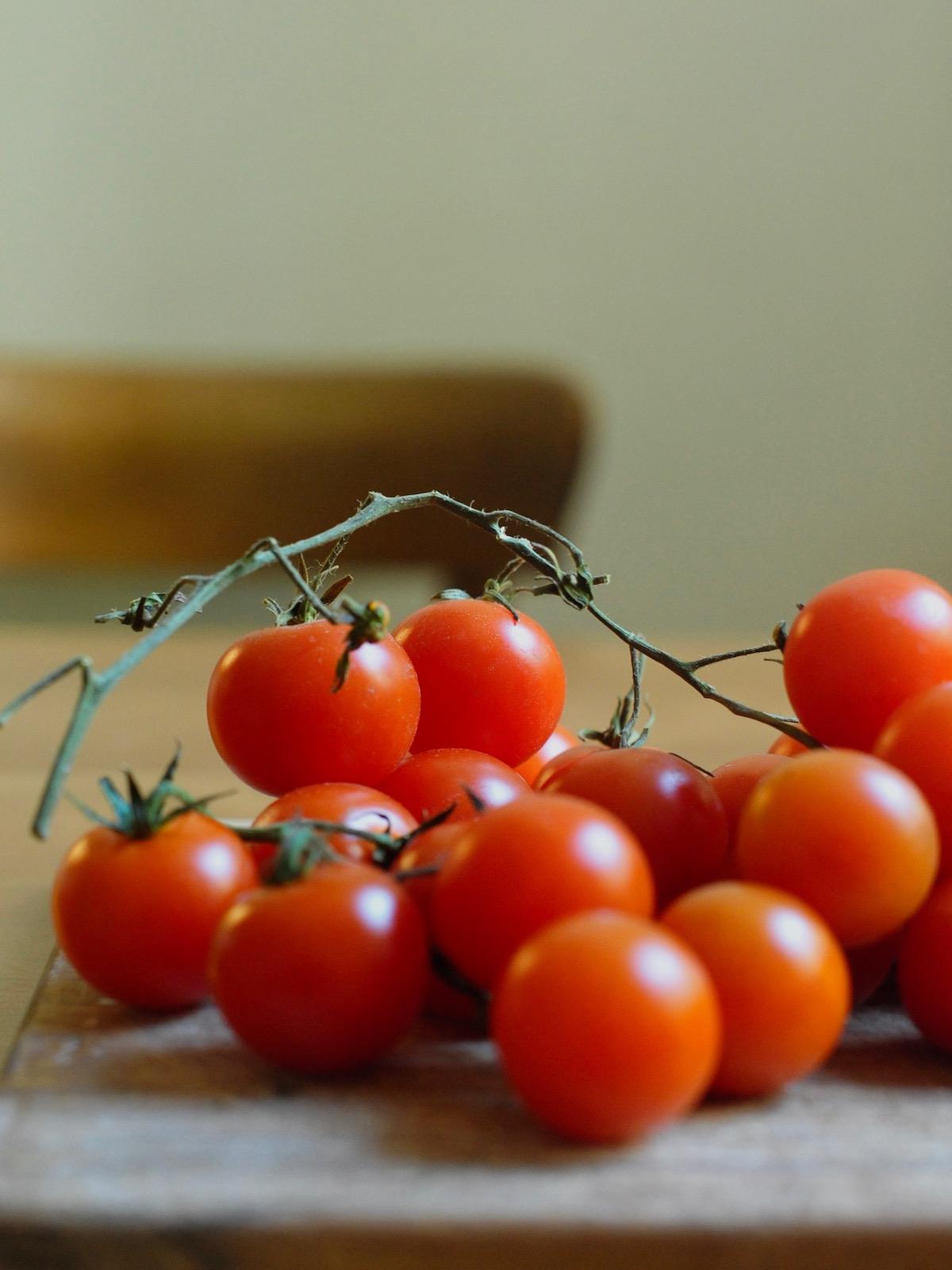 Rispe mit frischen Cherrytomaten auf Brett