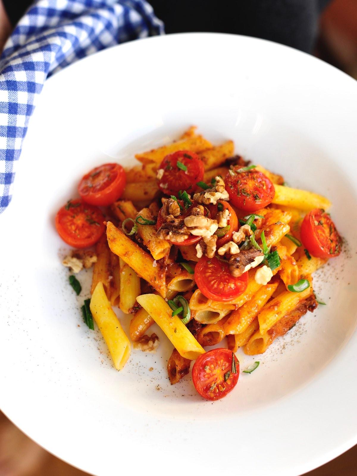 Teller mit frischer Pasta, rotem Pesto und karamellisiertem Tomaten