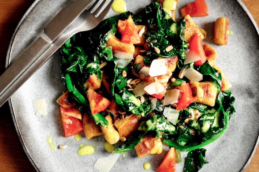 Teller mit selbstgemachten Kartoffelgnocchi mit Spinat und Tomaten