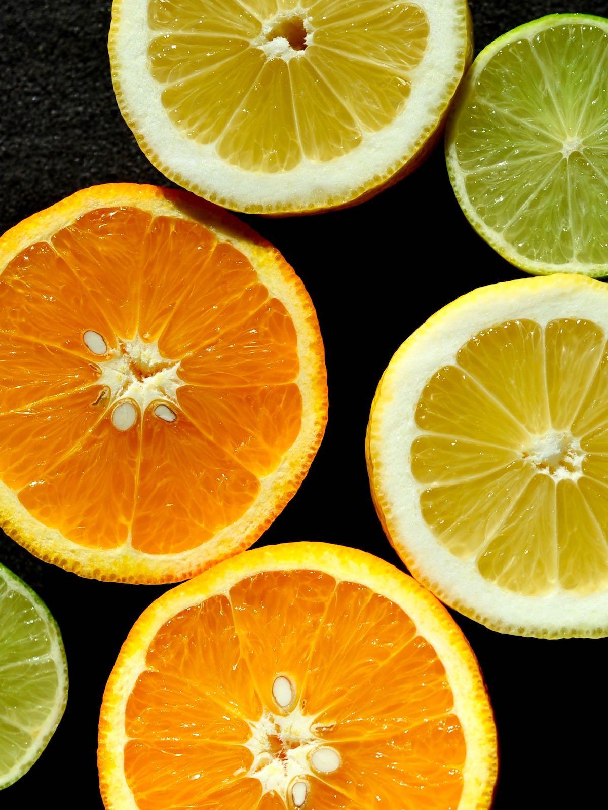 Orangen, Zitronen, Limetten auf schwarzem Untergrund