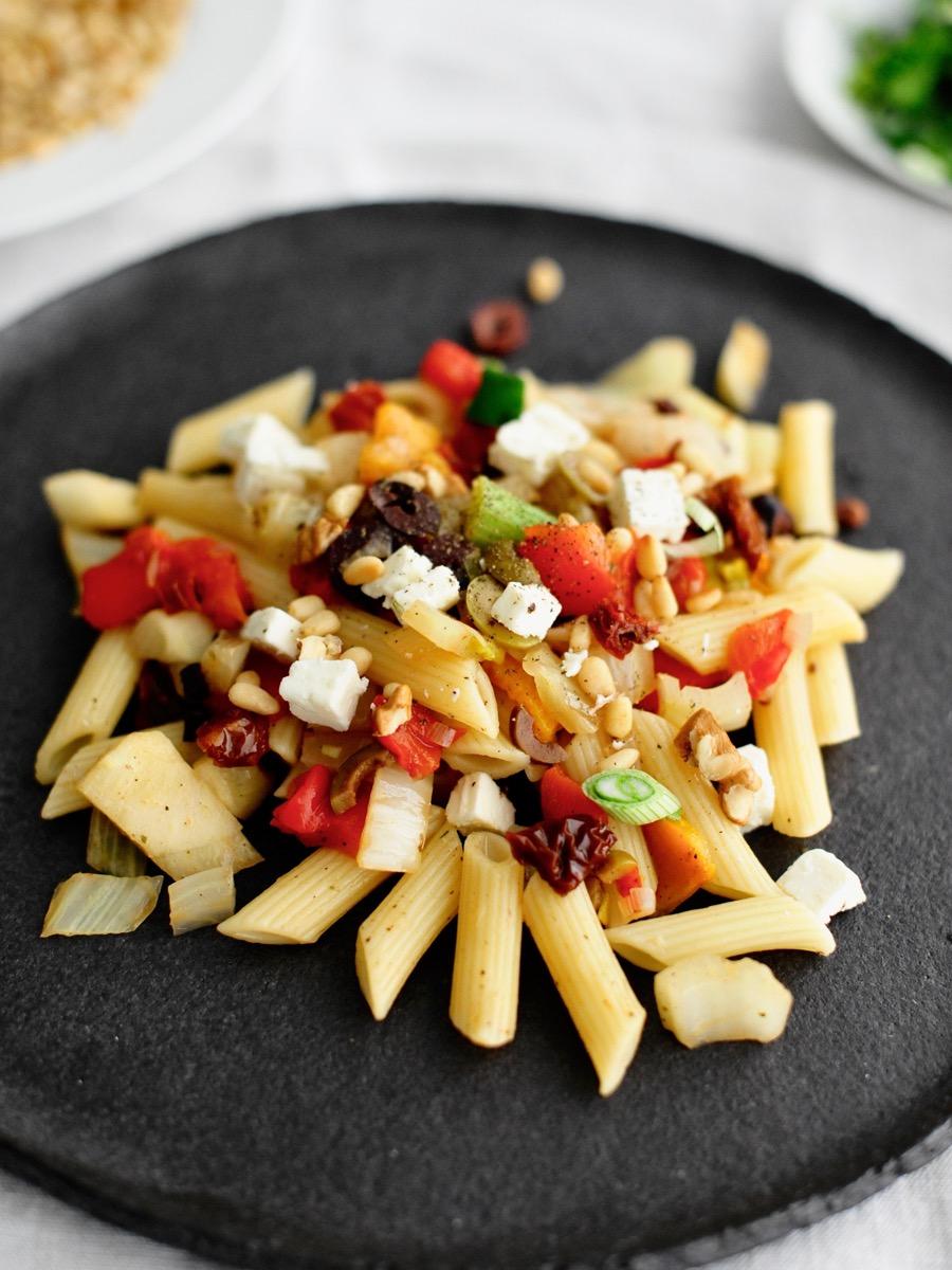 Teller mit Pasta und Paprika-Fenchel-Ragout und Oliven, Pinienkernen, getrockneten Tomaten