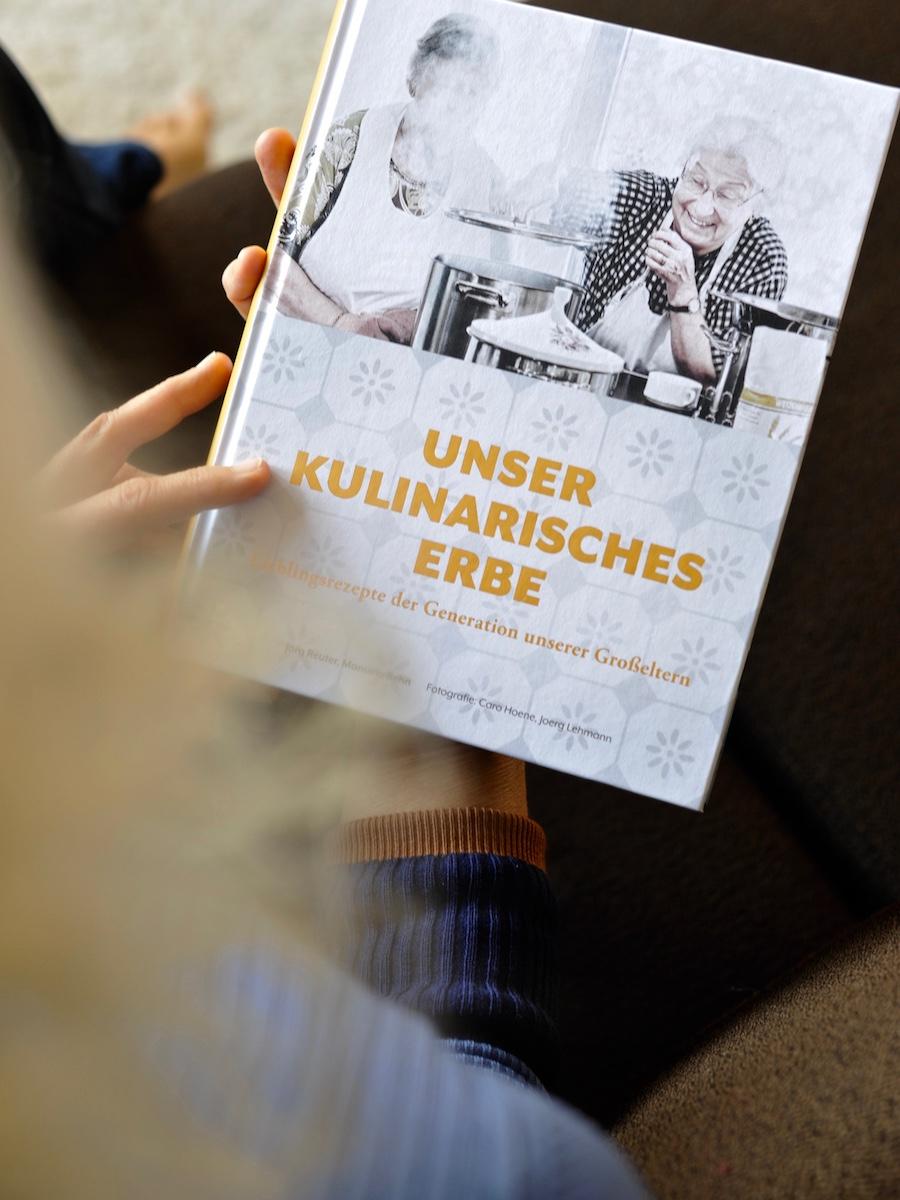 Frau auf Sofa mit Kochbuch Mein kulinarisches Erbe von Manuela Rehn und Jörg Reuter