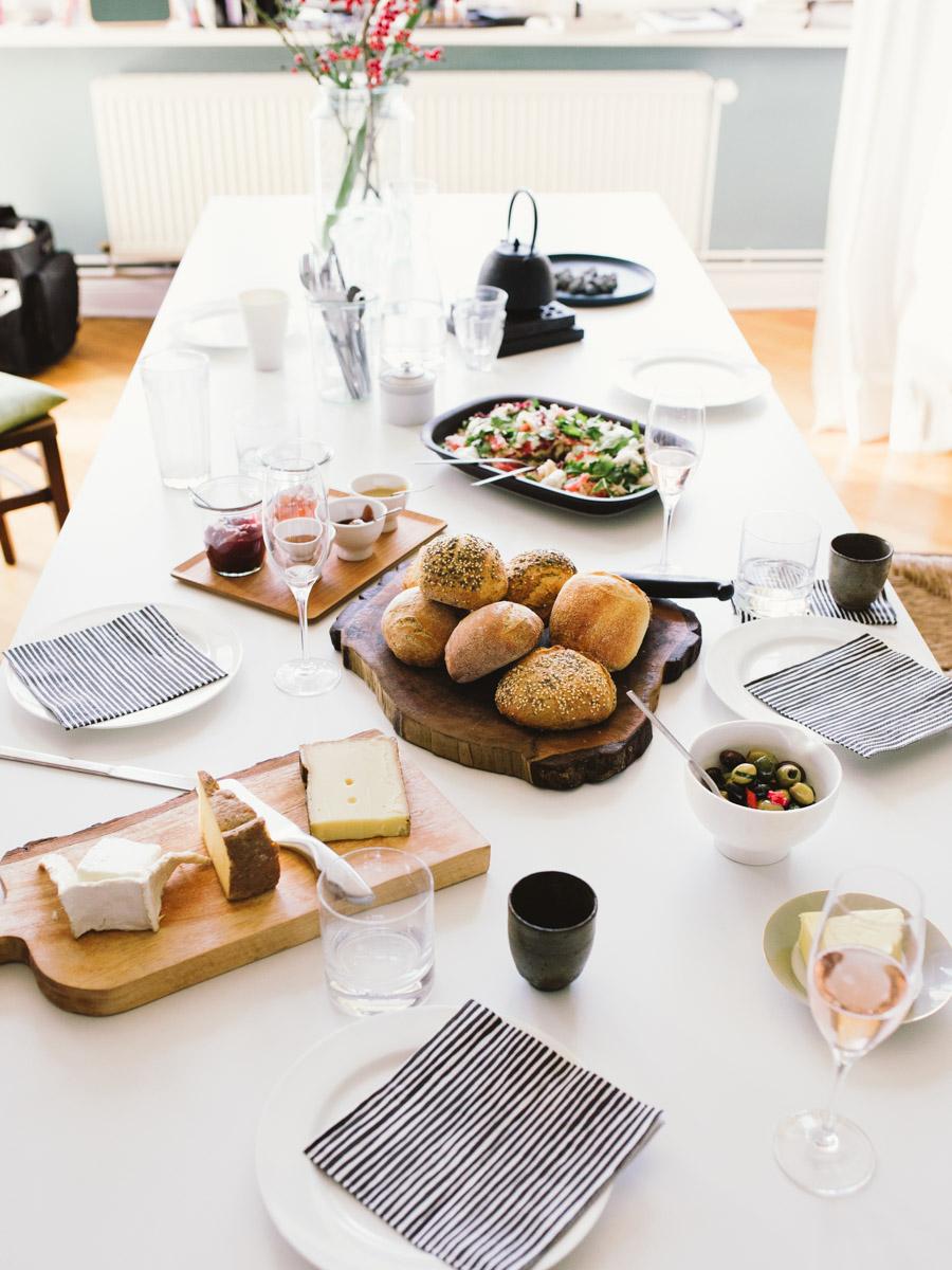 Gedeckter weißer Esstisch mit Brötchen, Marmelade, Kaese und Salat
