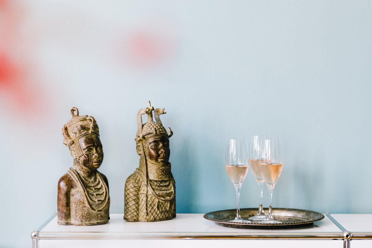 Prosecco in Gläsern auf Sideboard mit afrikanischen Büsten