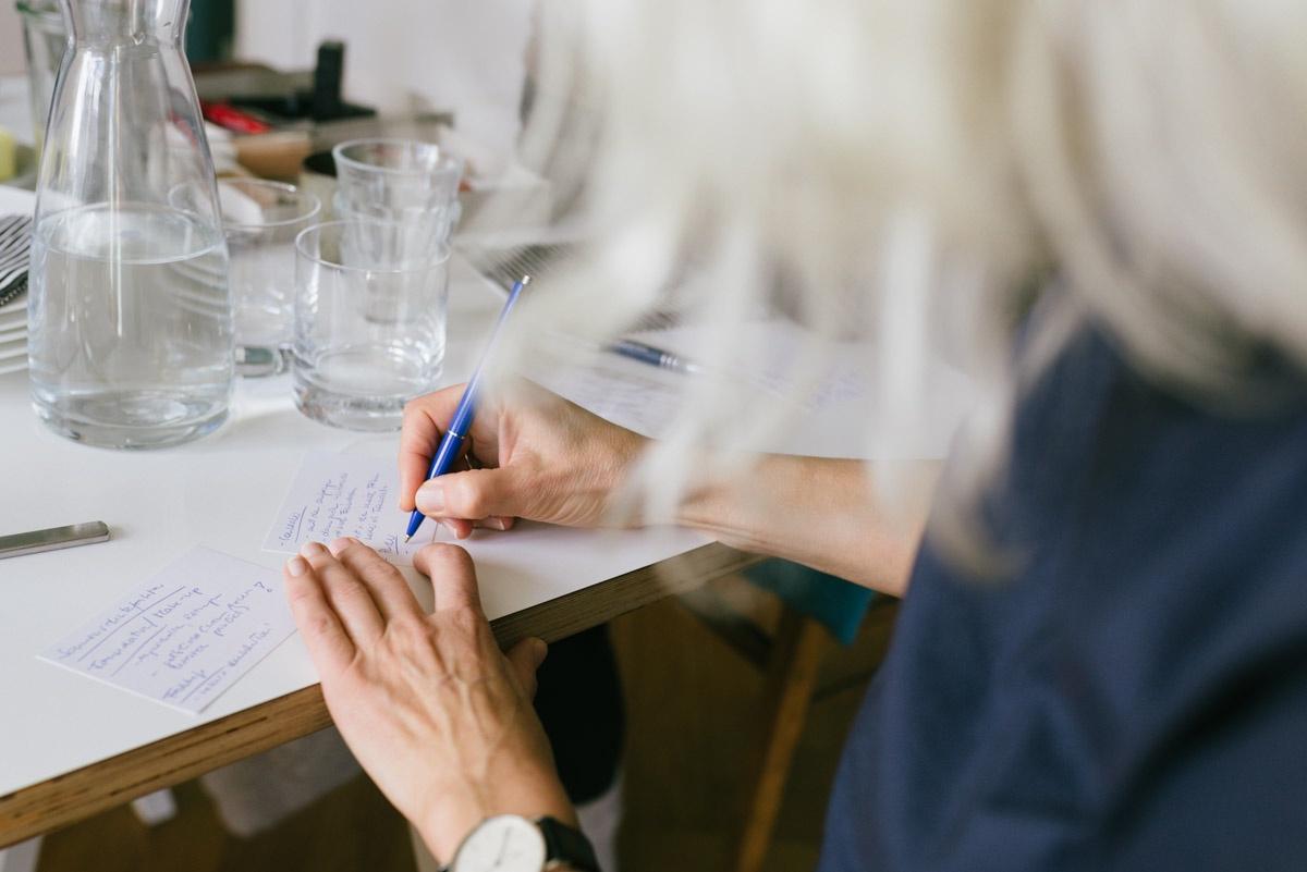 Claudia Hoffmann von Foodblog Ich esse fuer mein Leben gern macht sich Notizen am Tisch