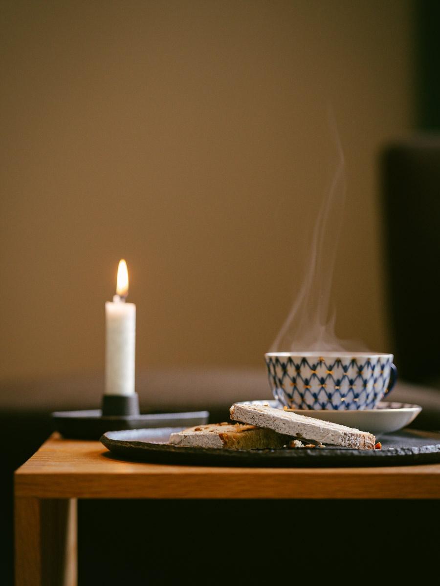 Brennende Kerze mit Bremer Klaben und Tee auf Tischchen