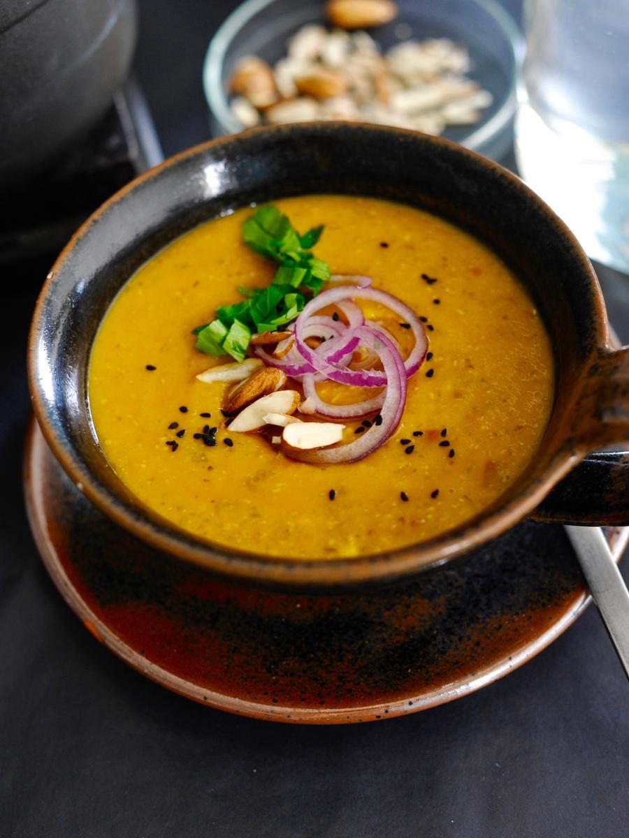 Suppenschale mit Dal tadka, Zwiebeln, Mandeln und Petersilie