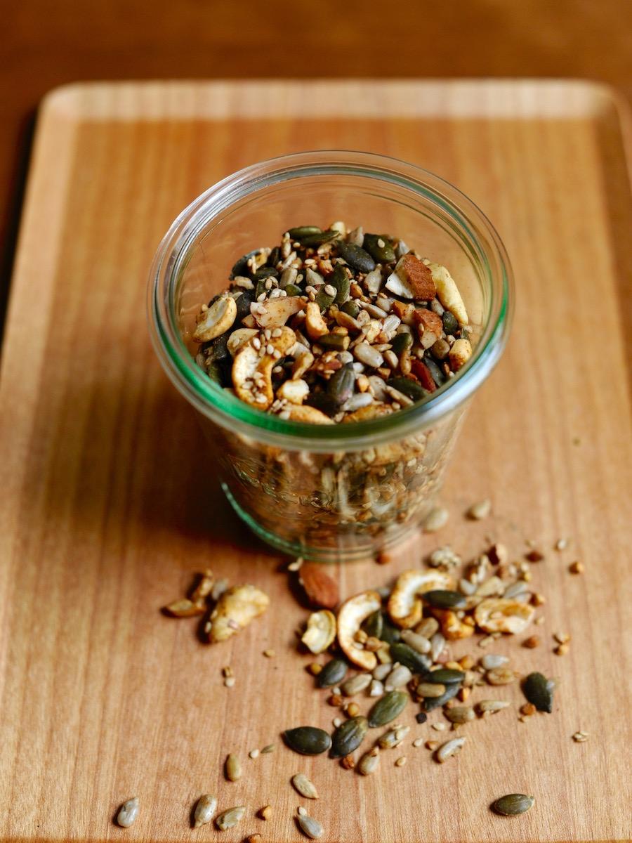 1 Glas Nussgranola auf einem Tablett mit gerösteten Nüssen, Samen, Kernen und Anis