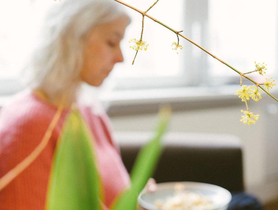 Blick durch einen Zweig auf eine Frau beim Essen auf dem Sofa
