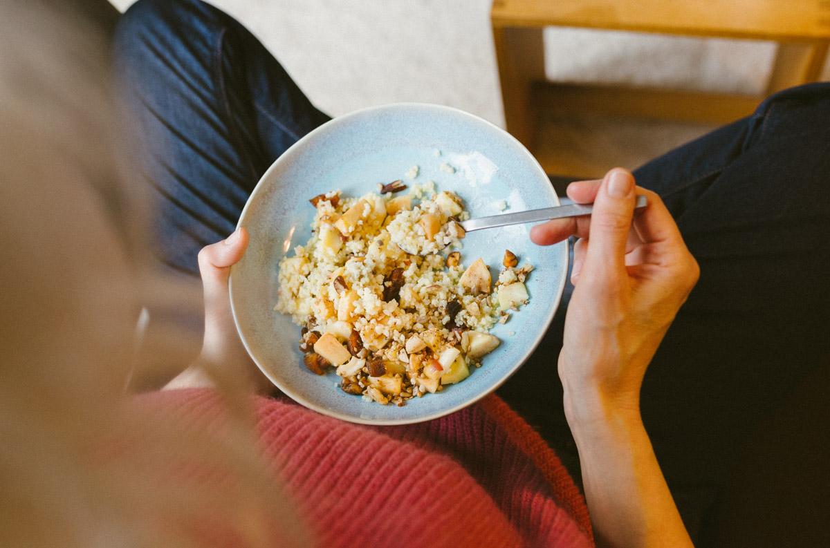 Frau isst auf dem Sofa einen Hirsebrei mit Obst und Nussgranola