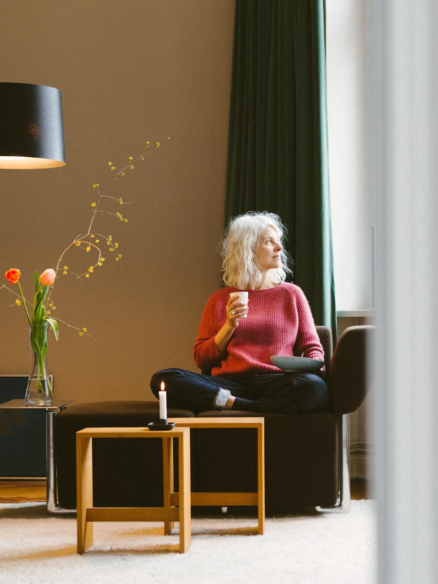Frau auf Sofa mit einem Becher Tee in der Hand