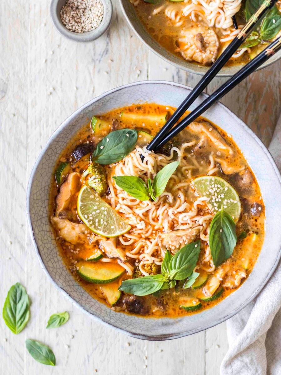 Bowl mit thailändischer Erdnuss-Nudelsuppe und Kräutern