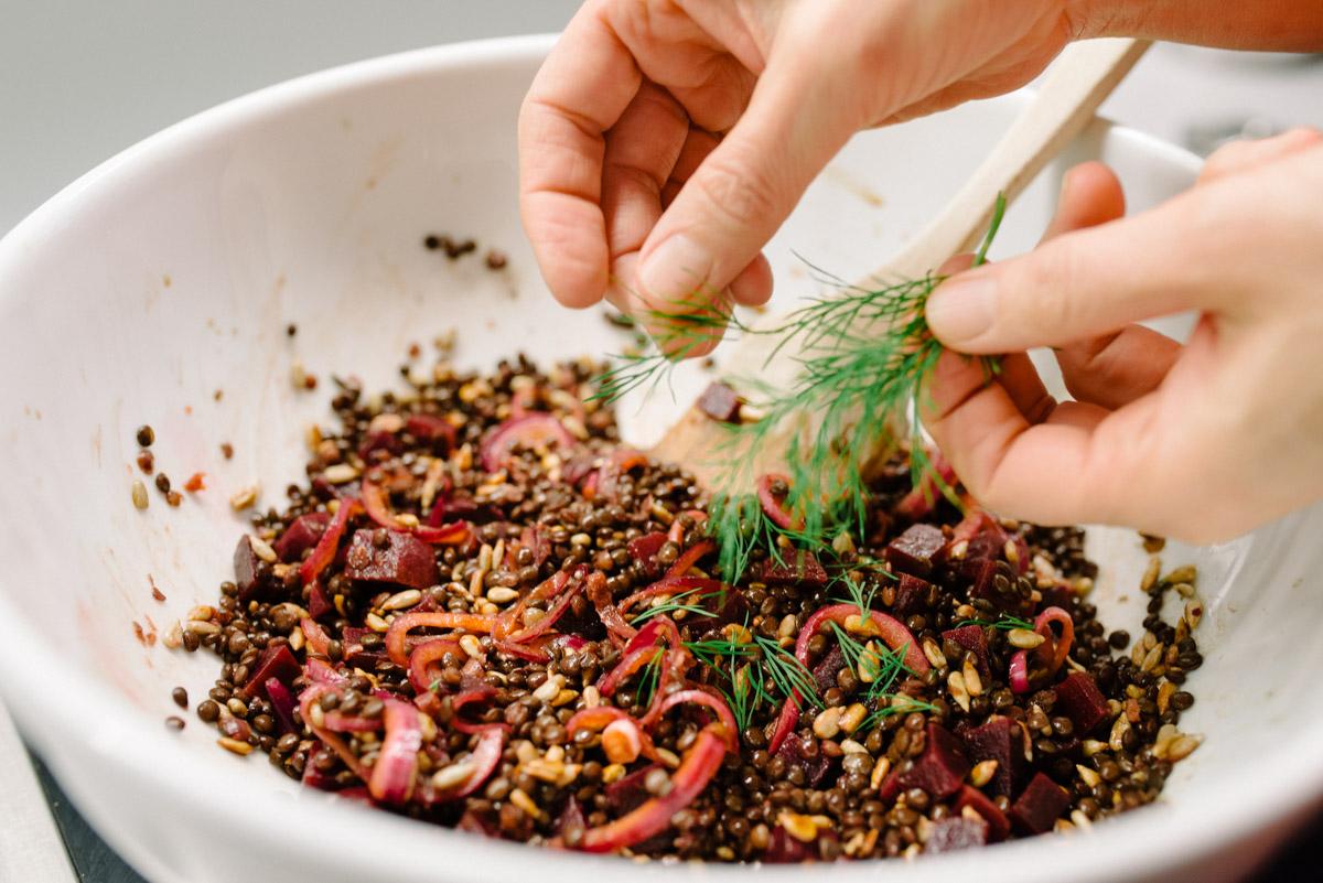 Frau zupft Dill in Linsen-Salat