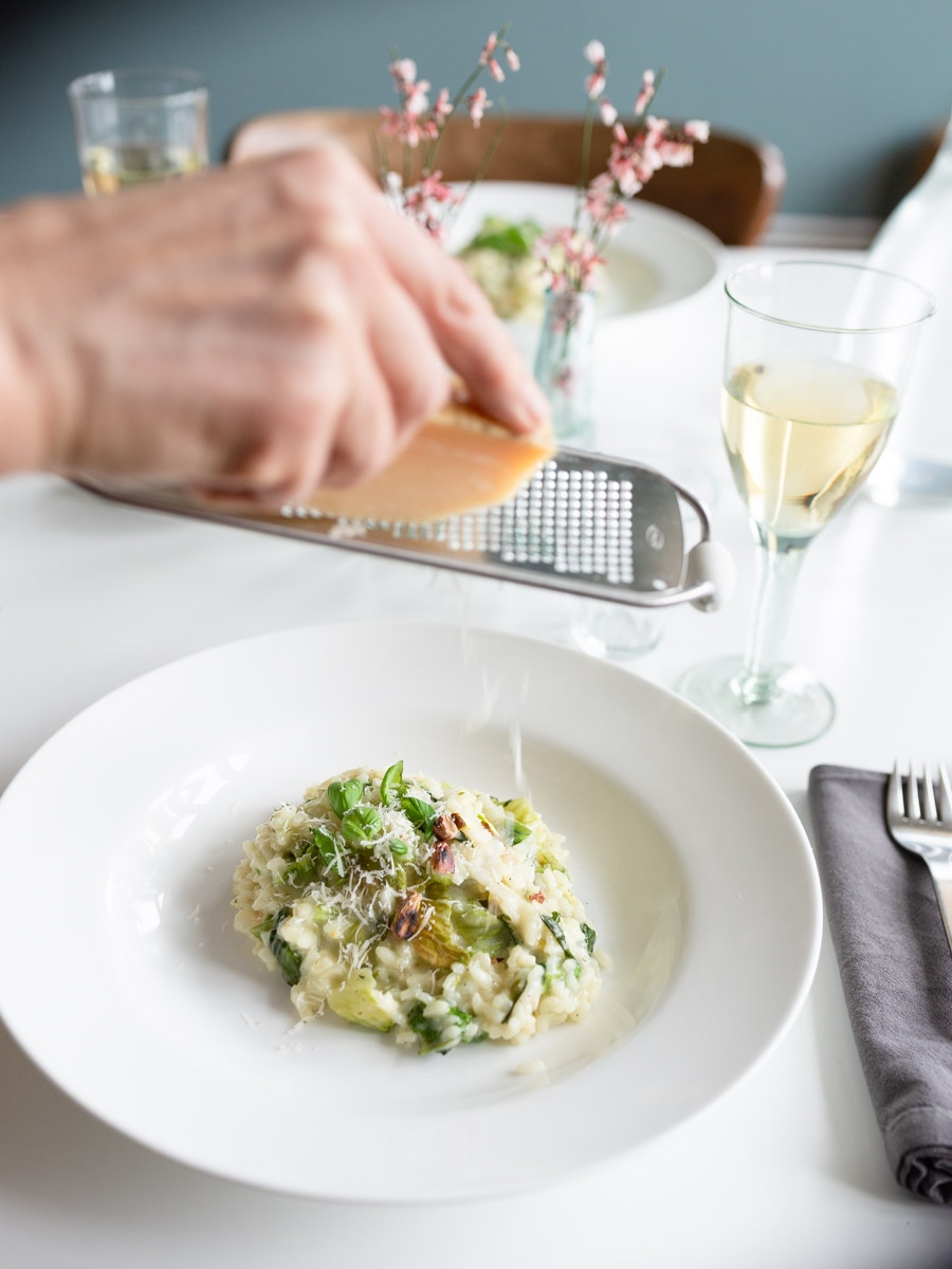 Frau reibt Parmesan auf ein Risotto mit Kopfsalat