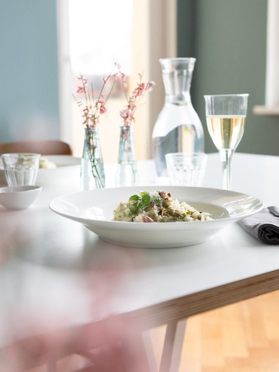 Festlich gedeckter Tisch mit weißem Teller mit Risotto und einem Glas mit Weißwein