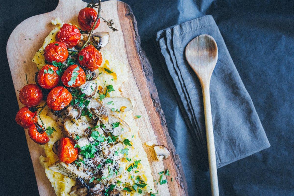 Polenta, Pilzen, gebackene Cherrytomaten hübsch angerichtet auf einem rustikalen Brett