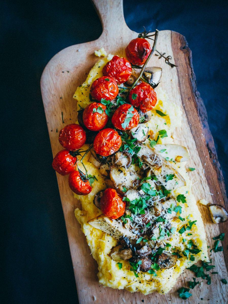 Rustikales Brett mit Polenta, Pilzen, Cherrytomaten, Parmesan und Petersilie als Topping