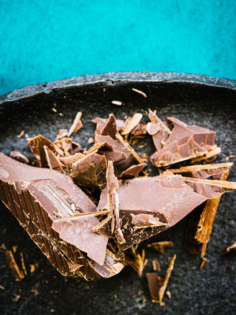 Große Splitter von Bitterschokolade auf dunkler Schale.