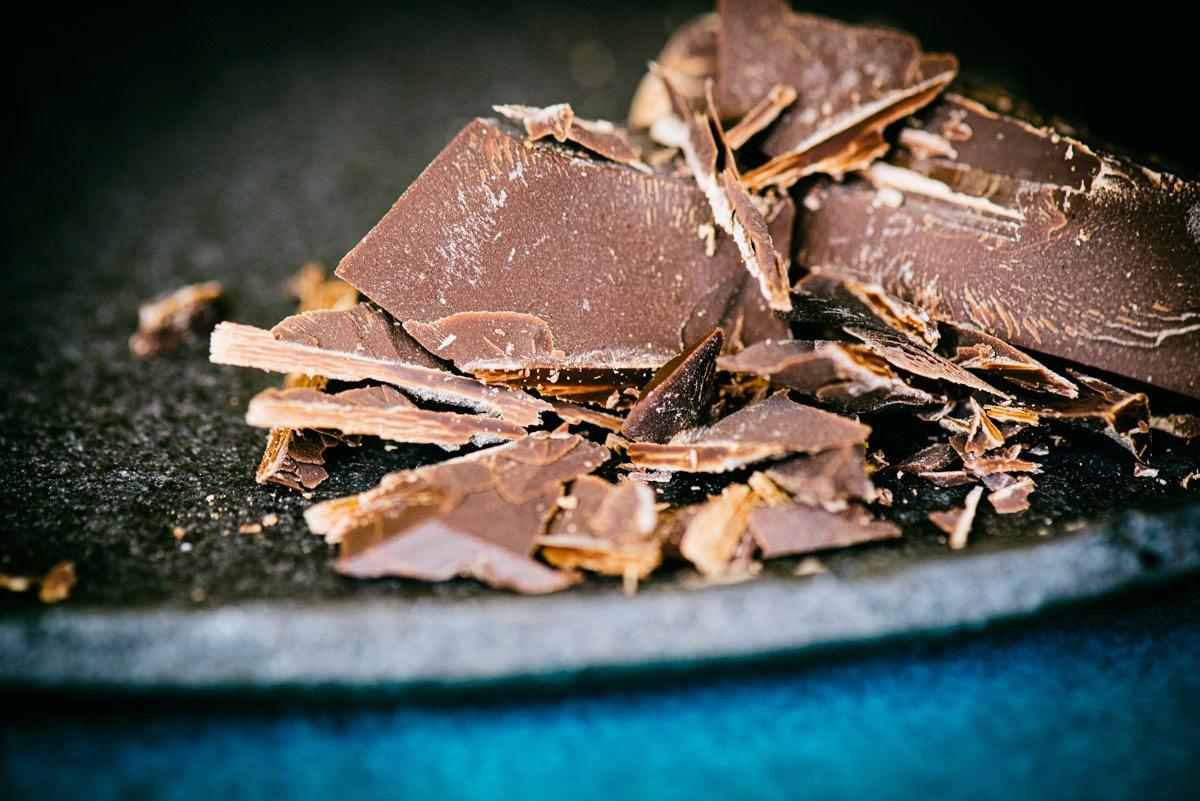Stückchen von Bitterschokolade auf dunkler Schale.