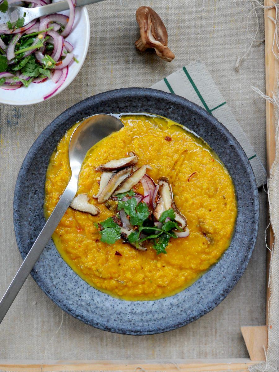 Schale mit pürierter Suppe und einem Topping aus roter Zwiebel, Pilzen, roter Zwiebel, Zitrone, Chiliflocken und Olivenöl