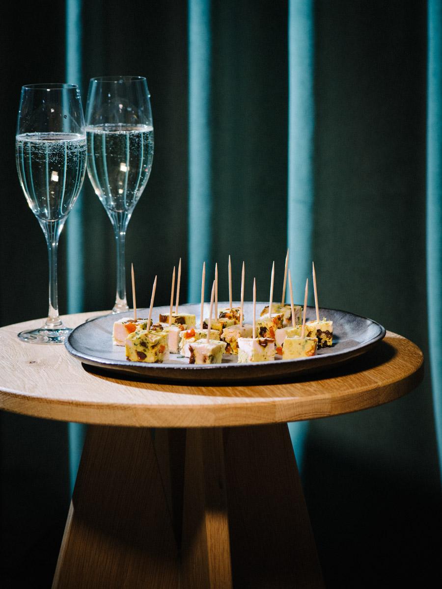 Hühnchenterrine auf Teller mit Sekt ist das perfekte Fingerfood-Rezept für besondere Anlässe