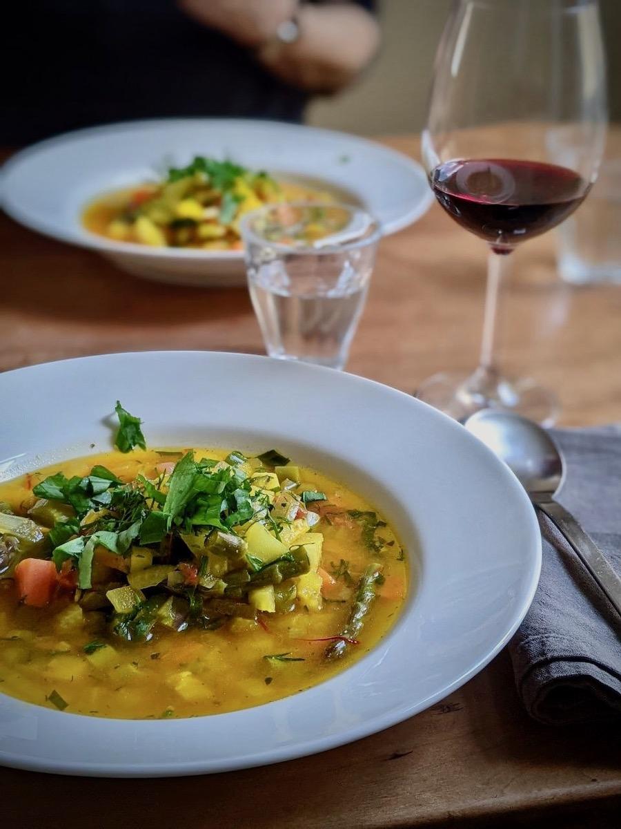 weißer Teller mit Gemüseeintopf Safran Lachs frische Kräuter