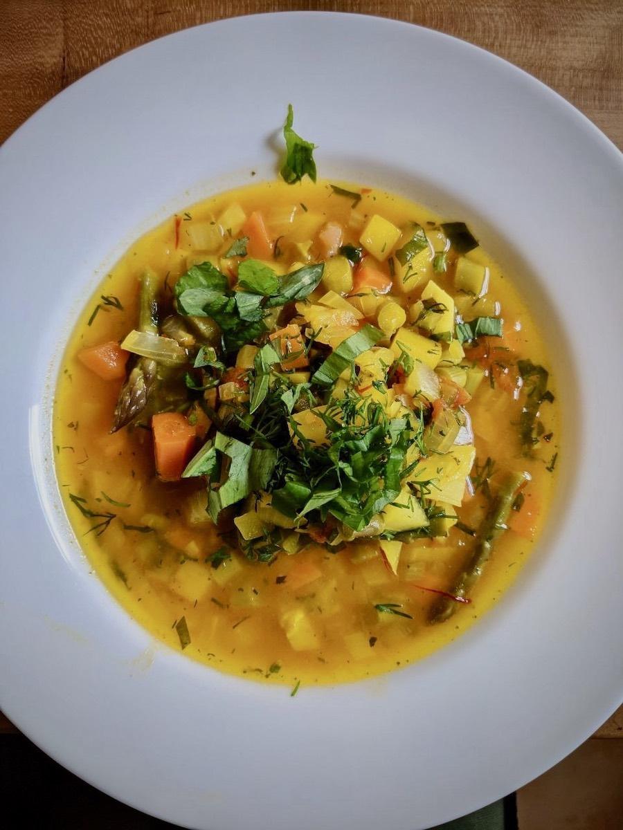 Teller mit Gemüseeintopf Safran Lachs frische Kräuter