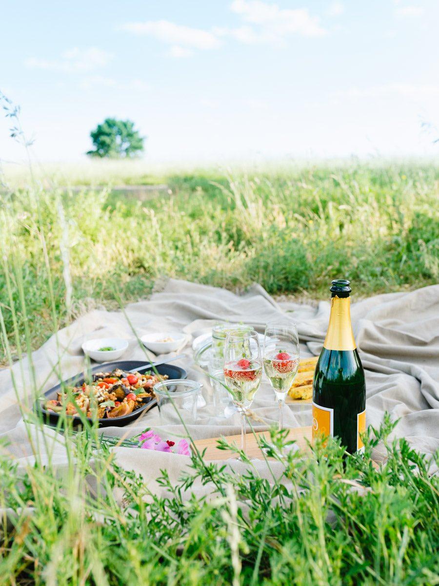 Picknickdecke mit Salat, Sekt und anderen Leckereien