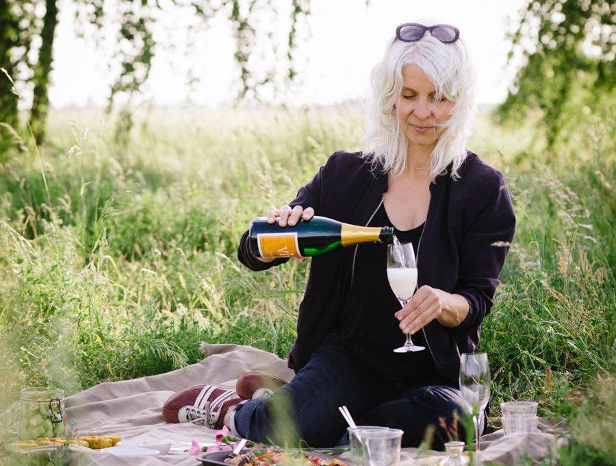 Frau sitzt auf Picknickdecke im Grünen und gießt Sekt in ein Glas