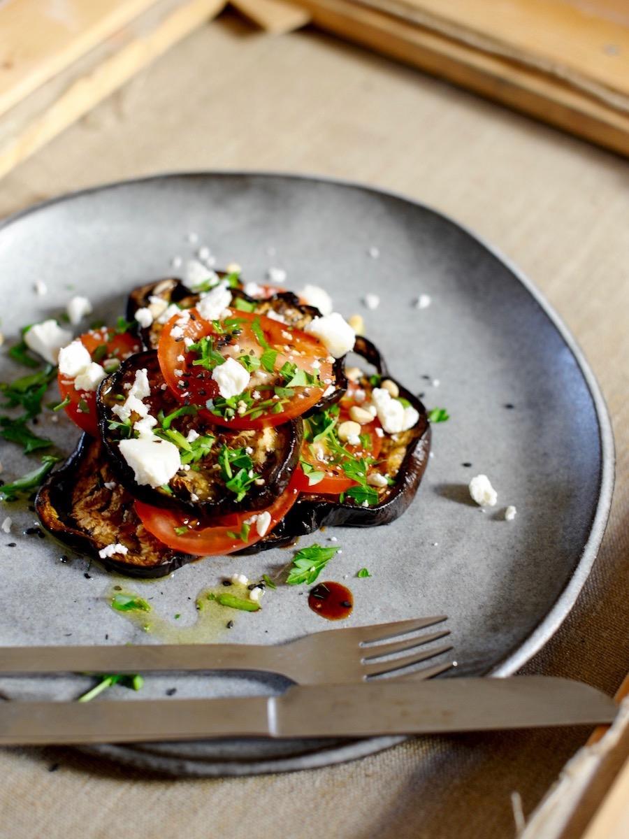 Teller mit butterweichen Auberginen, frischen Tomaten und Ziegenfrischkäse als leckeres Sommergericht
