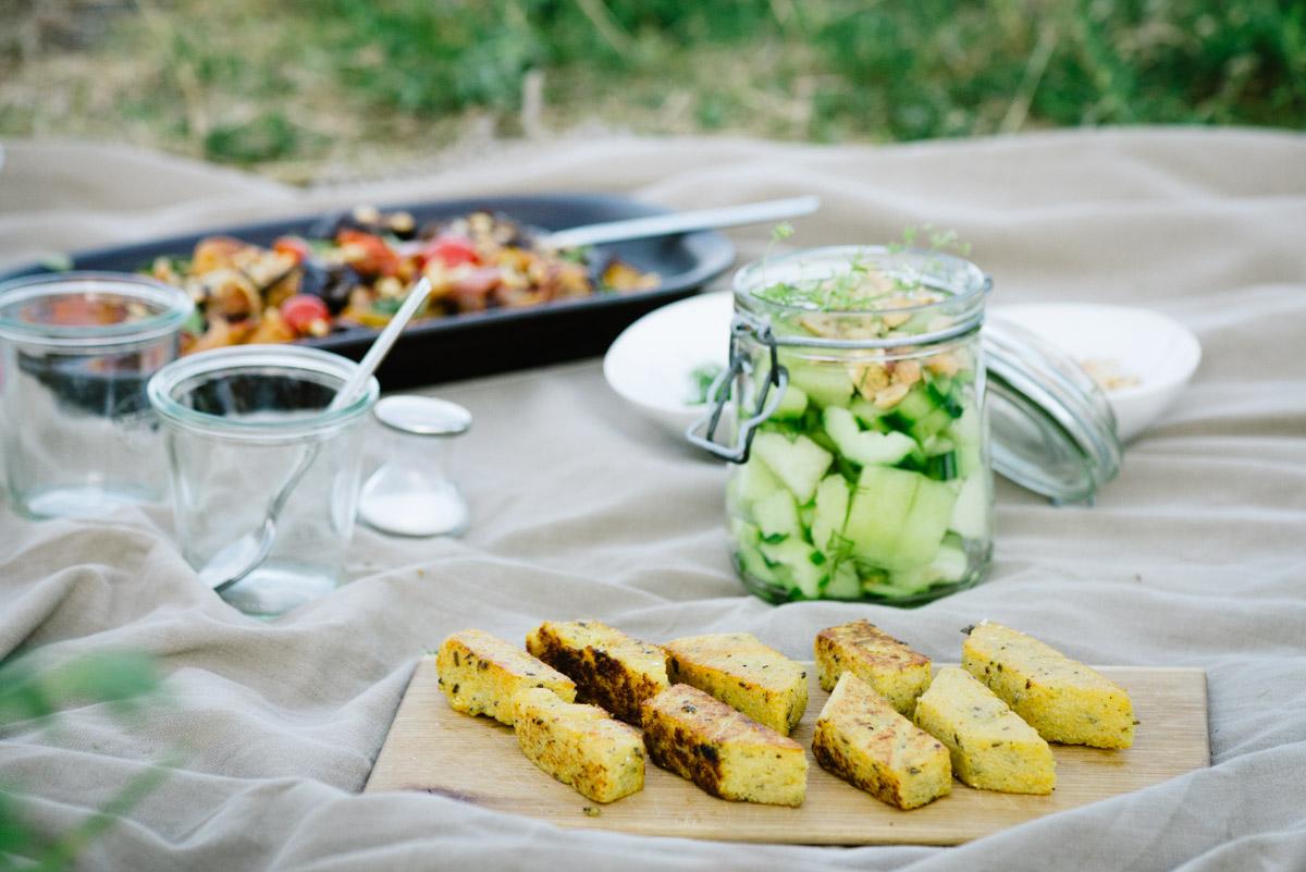 Gebratene Polentaschnitten und vegetarische Salate auf Picknickdecke