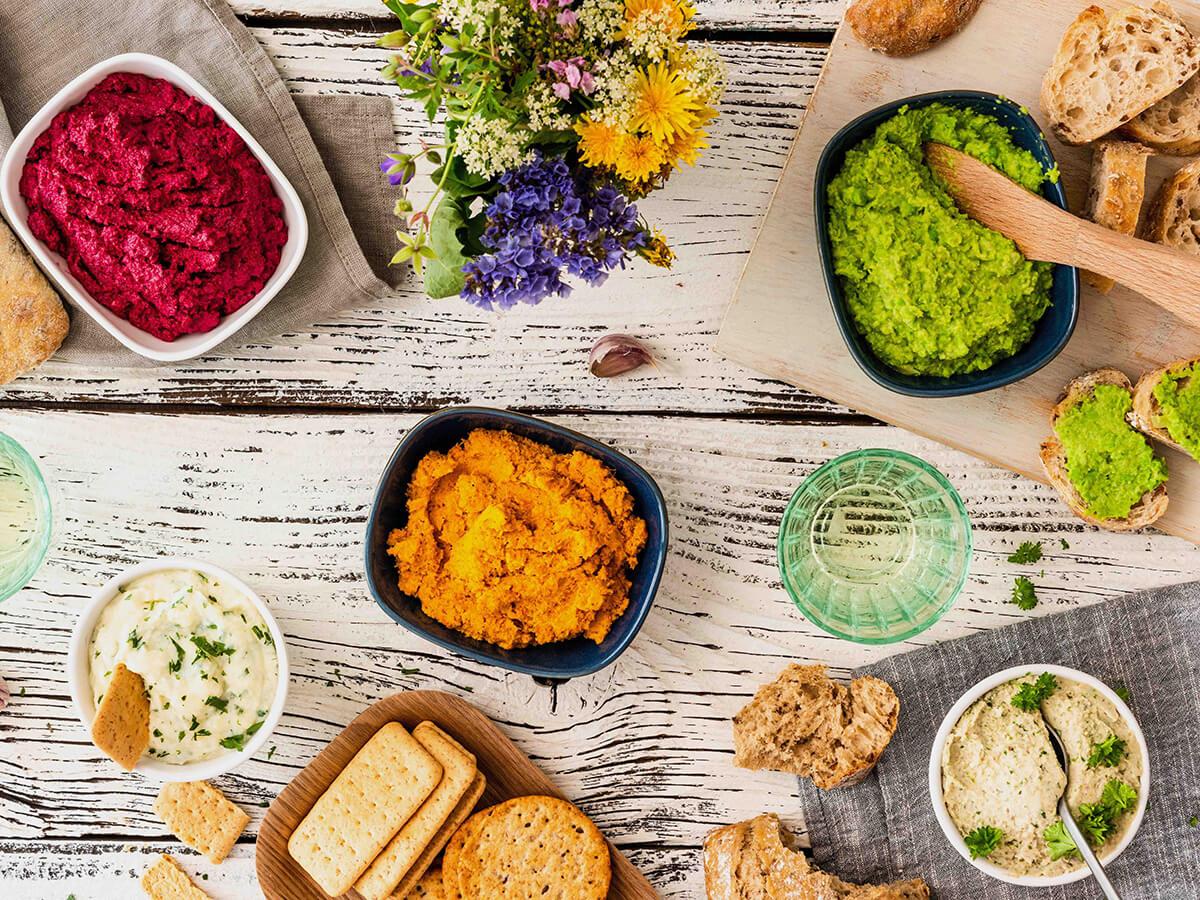 Schalen mit Brotaufstrich mit Rote-Bete-Walnuss, Kartoffel-Pastinakencreme, Ackerbohnendip und Erbsenaufstrich auf Brett