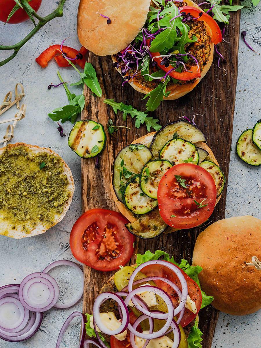 rustikales Holzbrett mit Grünkern-Burgerbrötchen, Gurkenscheiben, Tomatenscheiben, Zwiebelringen und Rucola